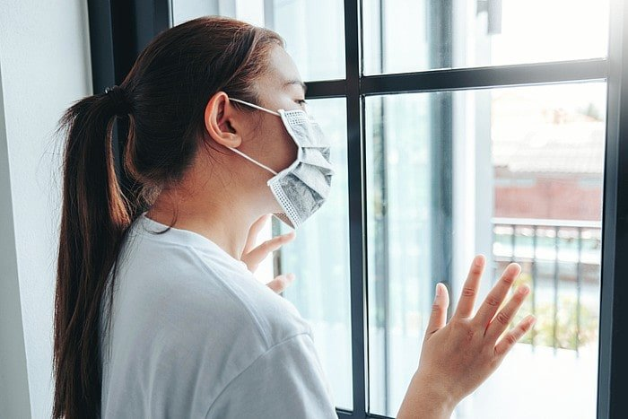 Lady wearing mask due to covid looking outside the window